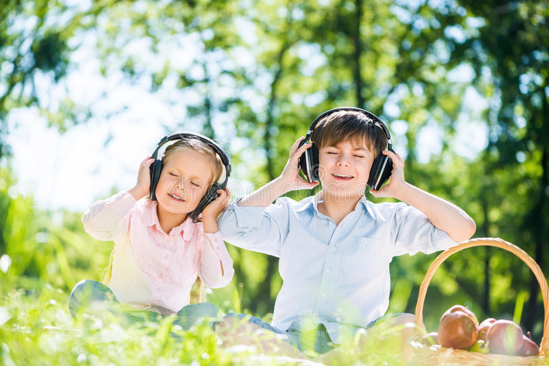 Children enjoying music. Little cute boy and girl in summer park royalty free stock images