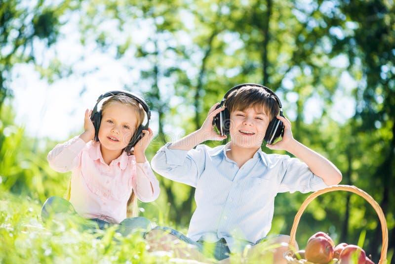 Children enjoying music. Little cute boy and girl in summer park royalty free stock photos