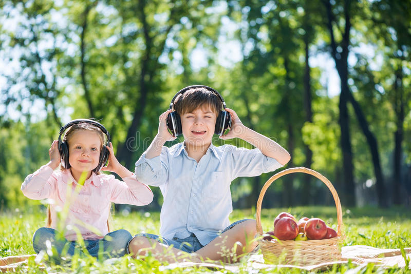 Children enjoying music. Little cute boy and girl in summer park stock images