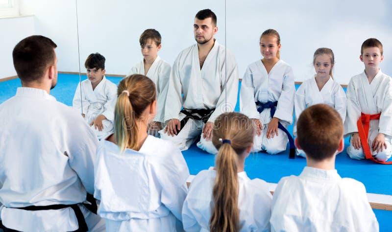 Children enjoying their trainings with coach at karate. Smiling children enjoying their trainings with coach at karate class royalty free stock image