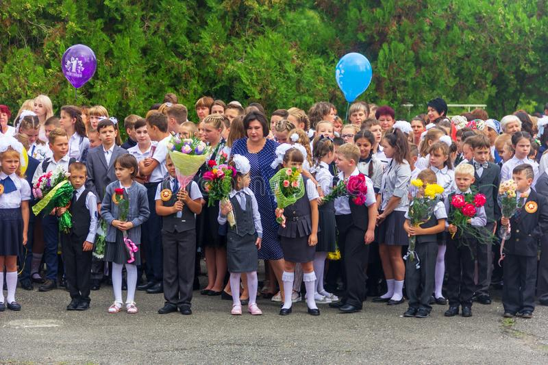 Children enrolled in the first class with bouquets of flowers in the hands, teachers and high school students on the school`s sol. Adygea, Russia - September 1 stock photography