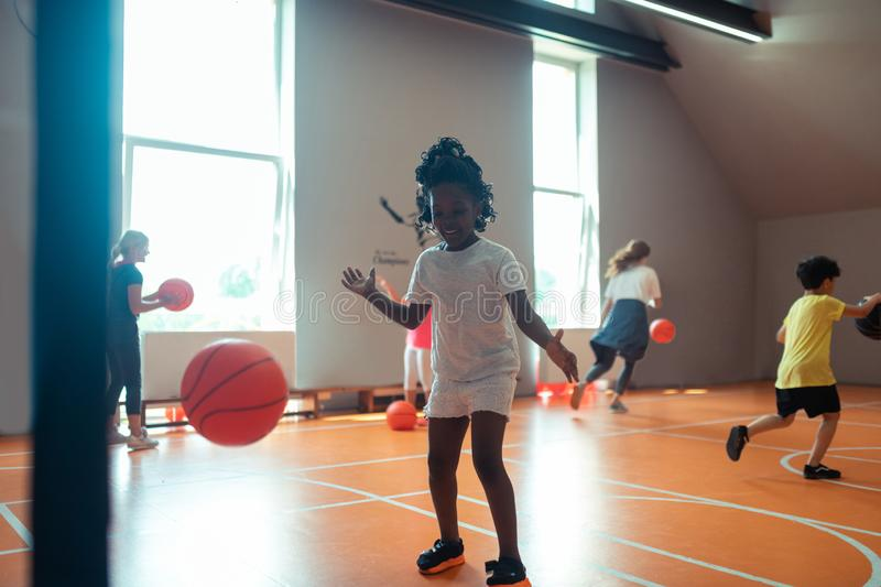 Children exercising with basketballs during sports class. Improving skills. Active children exercising with basketballs during their sports class in a spacious royalty free stock photo