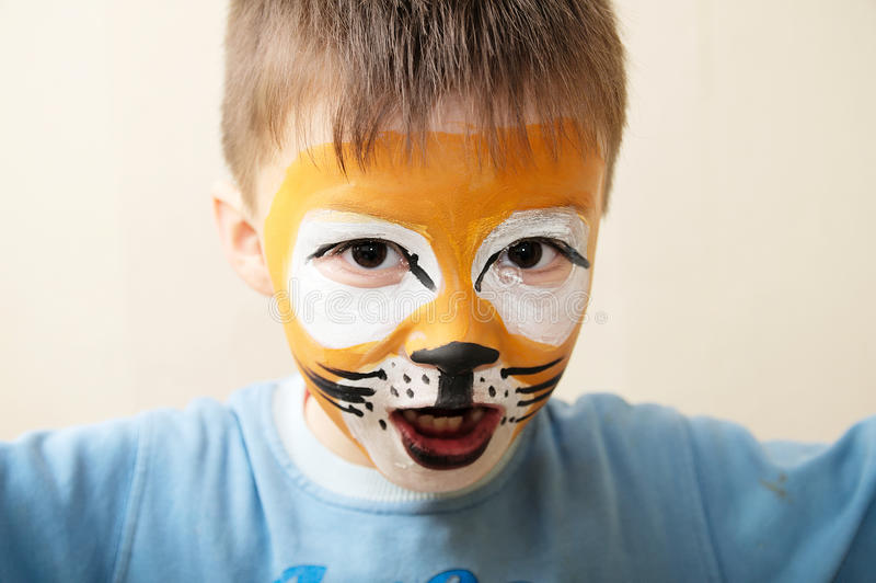 Children face painting. Boy painted as tiger or ferocious lion by make up artist. Preparing for theatrical performance stock photo