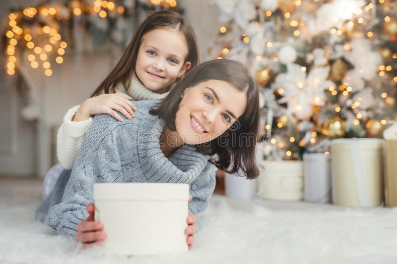 Children, family and celebration concept. Adorable female in knitted sweater holds white present box and small kid stands behind h. Er back, have good mood royalty free stock image
