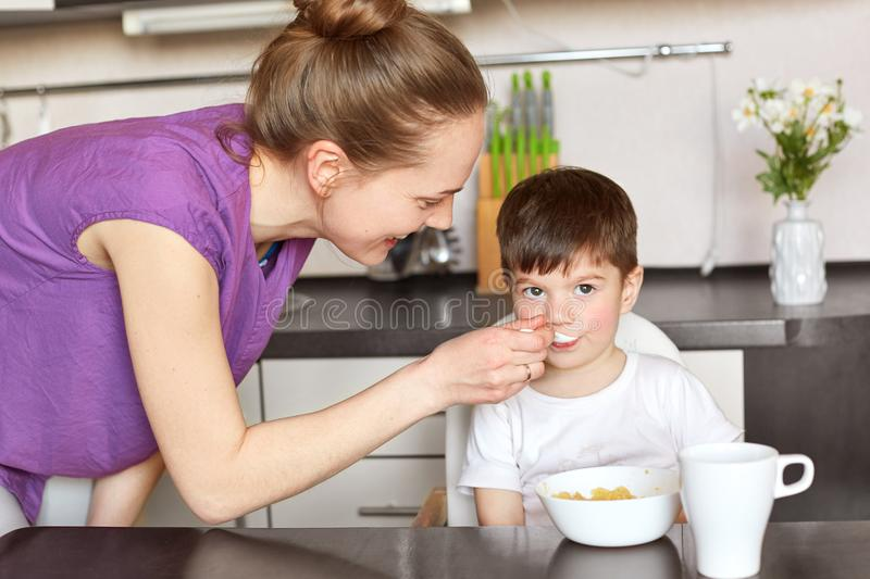 Children, family and eating concept. Portrait of delighted young cute female feeds her handsome little kid with delicious cereals stock photography