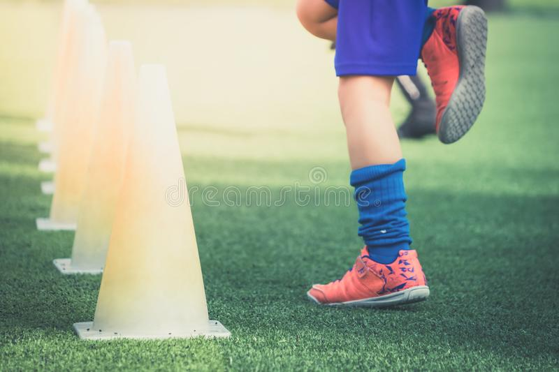 Children feet with soccer training on training cone on soccer ground royalty free stock image