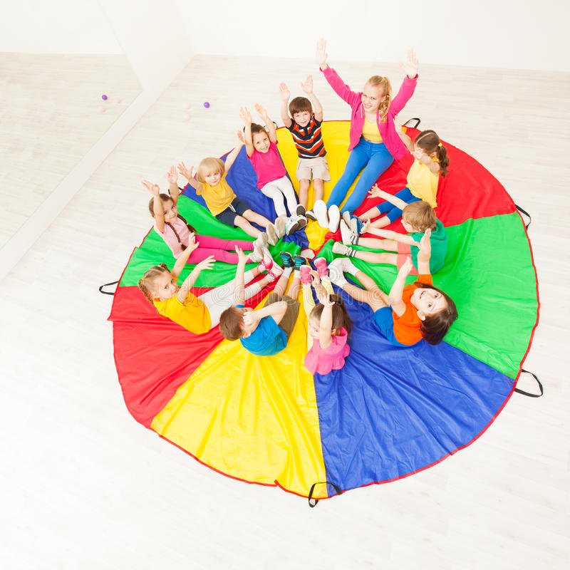 Children and female animator playing circle games. Top view portrait of happy children and female animator playing circle games, sitting on colorful parachute royalty free stock image