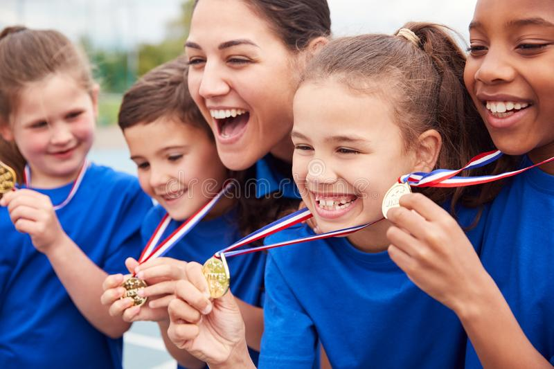 Children With Female Coach Showing Off Winners Medals On Sports Day royalty free stock photo