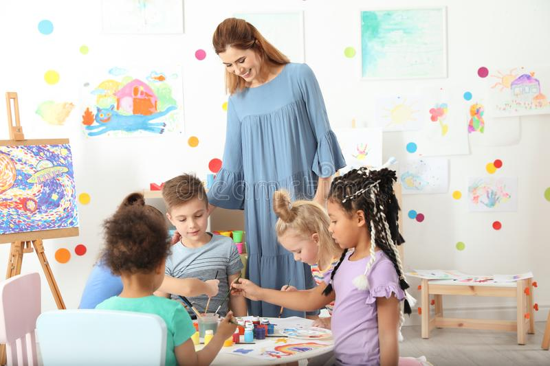 Children with female teacher at painting lesson stock photos