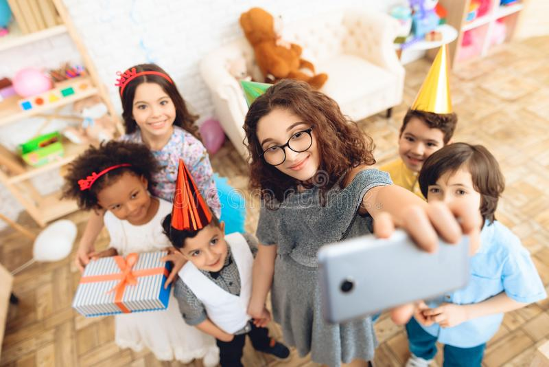 Children in festive attire and holiday hats make selfie, together at birthday party. stock image