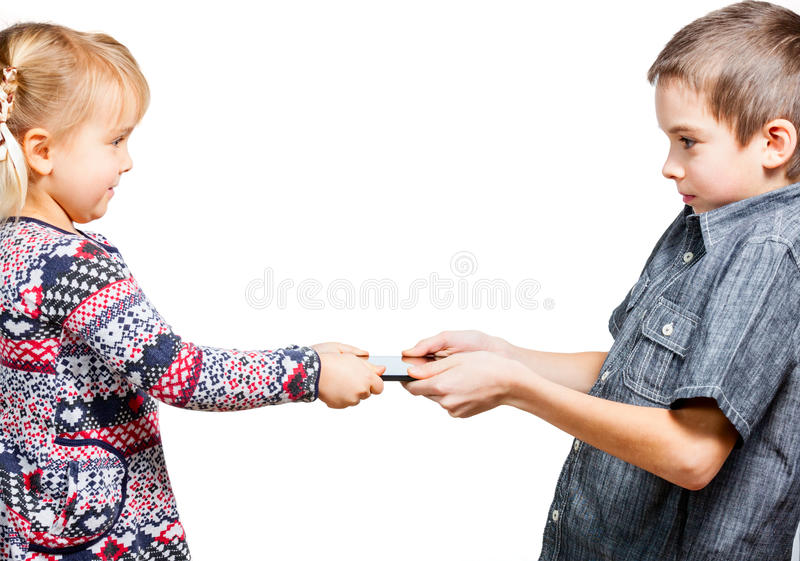 Children fight for tablet computer. Boy dont want to share a touch pad with little sister stock photo