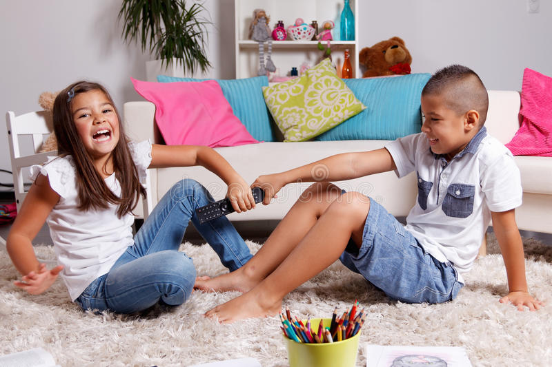 Children fighting over the remote control. Brother and sister fighting over the remote control in the living room royalty free stock images