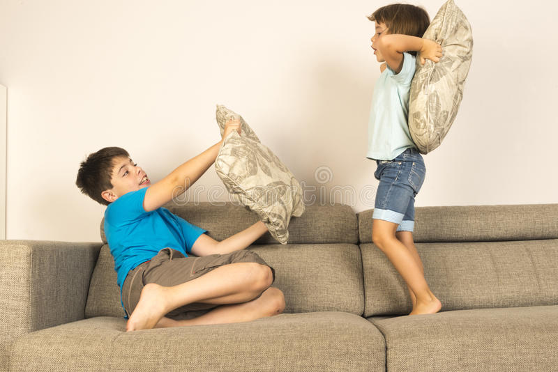 Children fighting together with pillows stock image