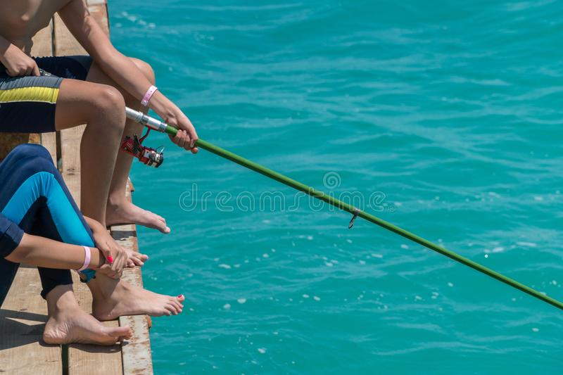 Children are fishing on the pier. Close-up of hands and rods royalty free stock photo