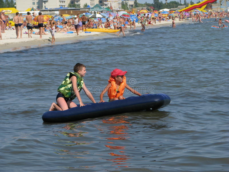 Children float on an inflatable mattress stock images