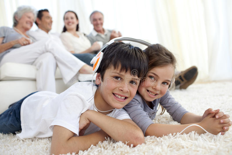 Children on floor listening to the music in livi. Smiling Children on floor listening to the music in living-room royalty free stock images
