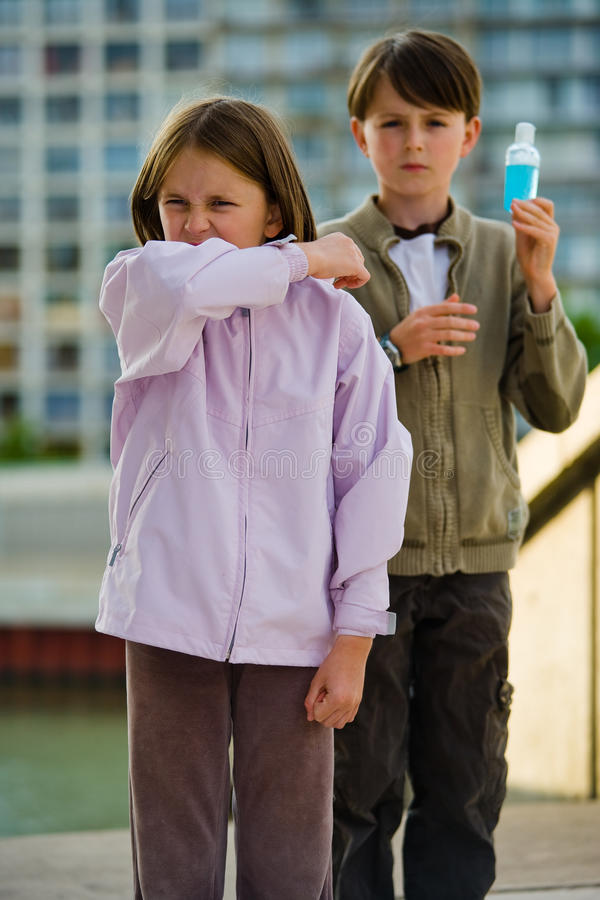 Children Flu Sneeze Elbow Sick. Two children stand in an urban setting, one sneezing into their elbow, the other holding a bottle of hand cleanser royalty free stock photo