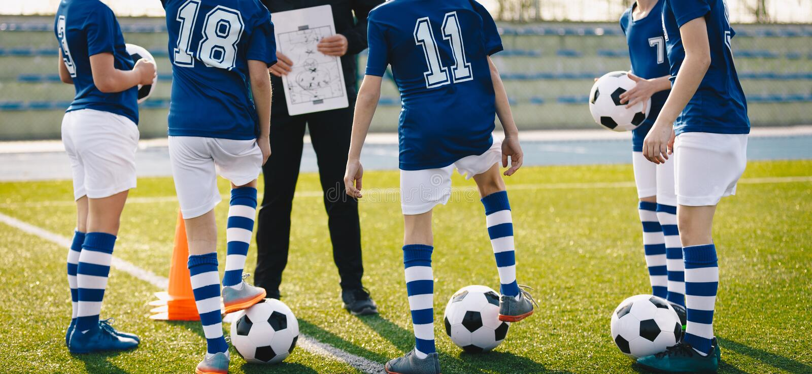 Children on Football Training. Young Footballers Listening Coach`s Pregame Speech. Coach Using Tactics Board Before Soccer Tournament Game royalty free stock photo