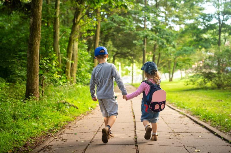 Children friendship. Kids walking in park together. Brother and sister hold hands. Baby friends royalty free stock image