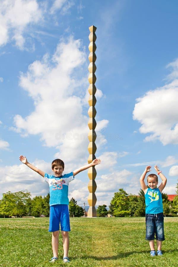 Children in front of The Endless Column or The Column of Infinity. The Endless Column, made by Constantin Brancusi in Targu Jiu, Romania symbolizes the Infinite royalty free stock photo