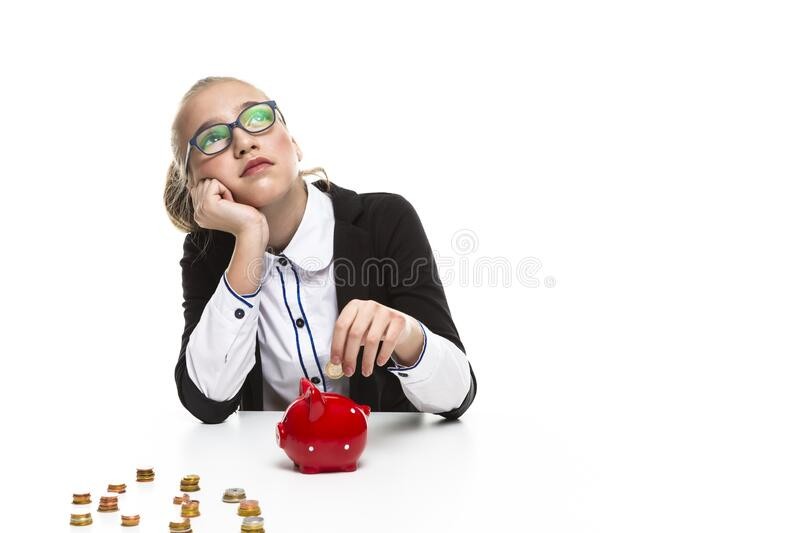 Children Frugal Concepts. Portrait of Thoughtful Dreaming Teenage Girl Wearing Glasses. Posing With Coins and Moneybox and Coins. Horizontal Image stock image