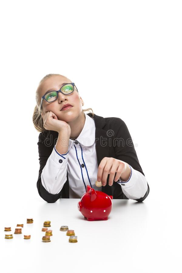 Children Frugal Concepts. Portrait of Thoughtful Dreaming Teenage Girl Wearing Glasses. Posing With Coins and Moneybox and Coins. Vertical Image royalty free stock photography