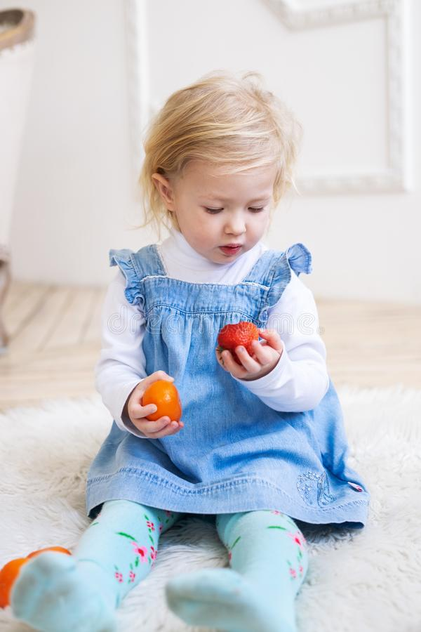 Children with fruits: A two-year-old little girl in a blue sundress holds red strawberries and an orange tangerine in stock photo