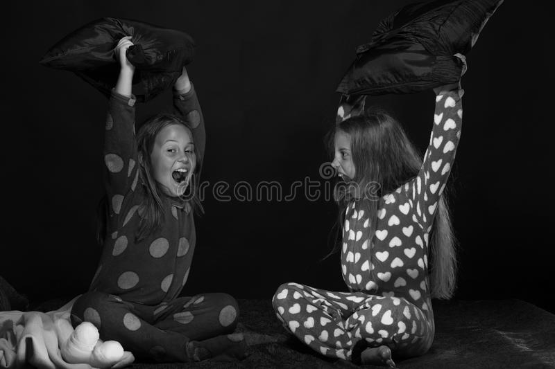 Children and fun time concept. PJs party for children: girls shouting and fighting with pillows. Children and fun time concept. PJs party for children. Girls stock photos