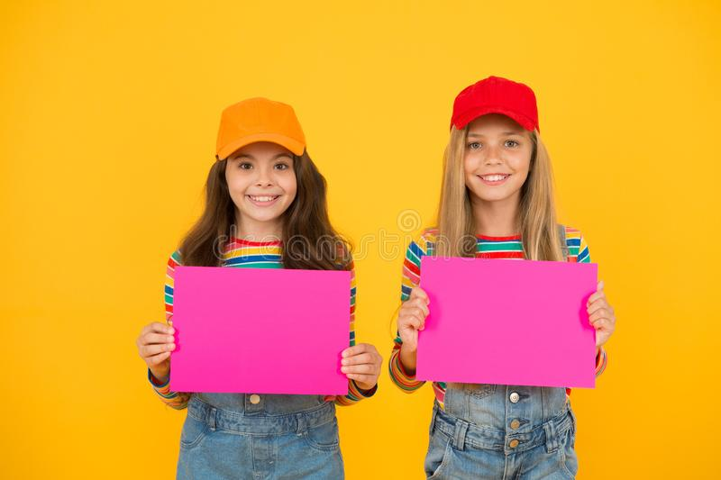 Children gallery modern art. Modern kids with pictures. Charity market. Girls hold modern poster blank pink paper sheets. Best friends copy space. Visual royalty free stock photos