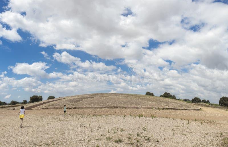 Children getting close to Dolmen de Soto burial mound, Huelva, S. Children getting close to Dolmen de Soto burial mound. This is the most importat megalithic stock image