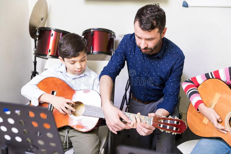 Children Getting Started On A Lifelong Journey Of Music. Instructor assisting boy to learn the fundamentals of guitar playing in music school royalty free stock photo