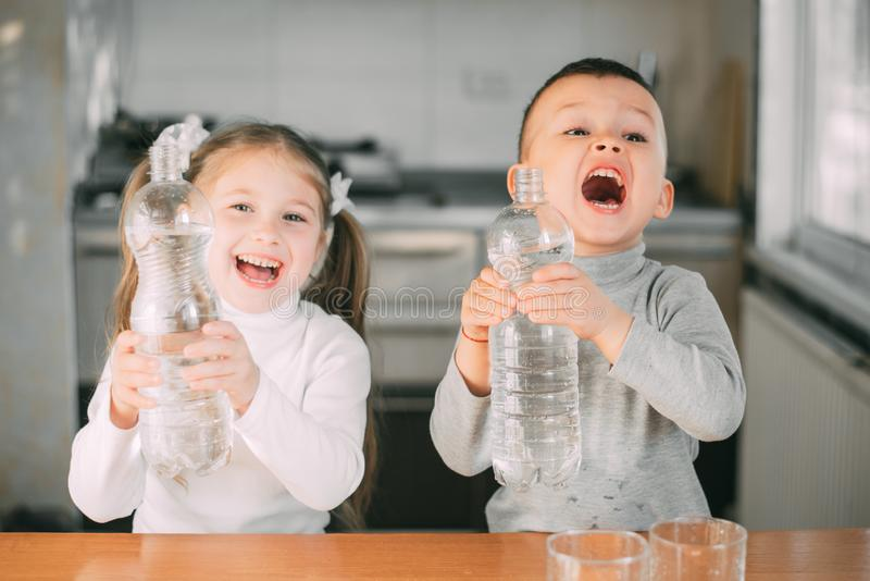 Children, a girl and a boy with bottles in his hands screaming thirst stock images