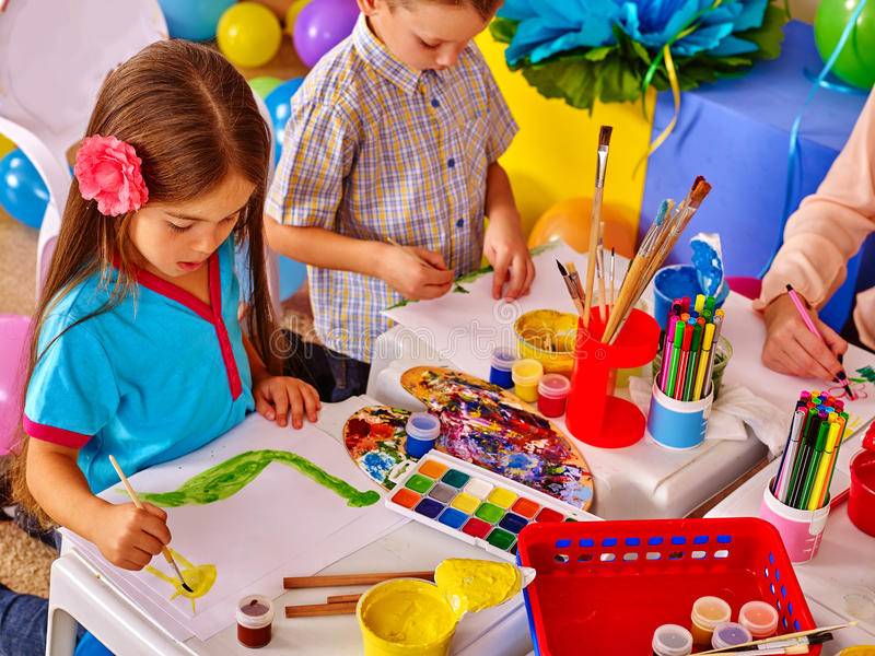 Children girl and boy with brush painting in primary school. stock photo