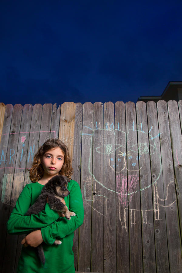 Children girl holding puppy dog on backyard wood fence