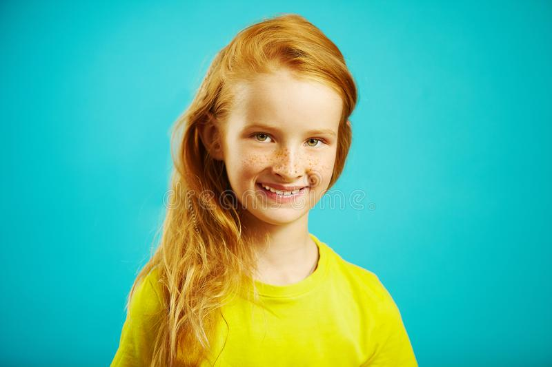 Children girl with red hair smiling sincerely on blue isolated background, expresses emotions of joy and happiness. Children girl with red hair smiling royalty free stock photography