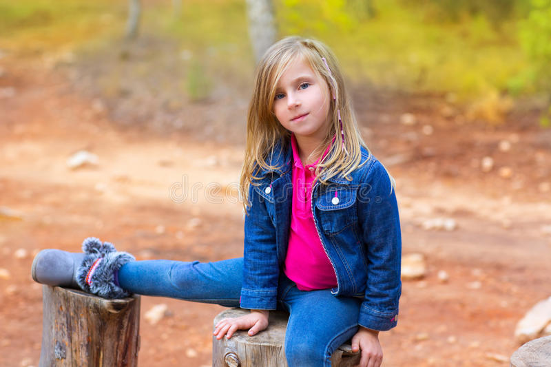 Children girl relaxed on a tree trunk stock photos