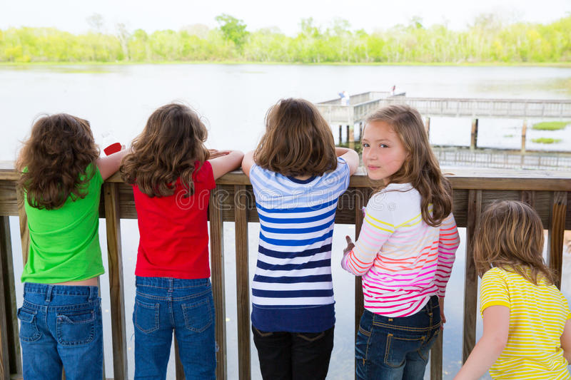 Children girls back looking at lake on railing stock images