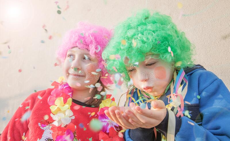 Children girls celebrate carnival smiling and having fun with  colorful confetti royalty free stock photo