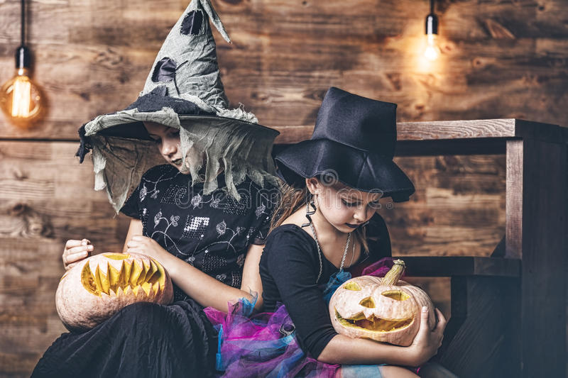 Children girls costumes witches with pumpkins and treats in the stock images