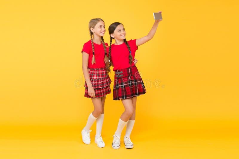 Children girls hold smartphone. Taking selfie photo. Fashion blog. Blog online. Smartphone application concept. Blogger stock images
