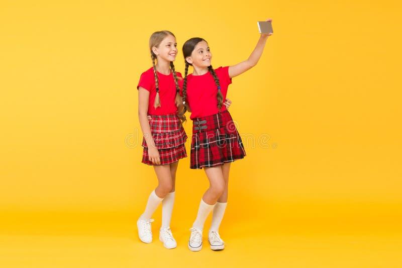 Children girls hold smartphone. Taking selfie photo. Fashion blog. Blog online. Smartphone application concept. Blogger. On social networks. Digital technology royalty free stock photography