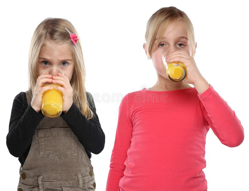 Children girls kids drinking orange juice healthy eating portrait format isolated on white. Children girls kids drinking orange juice healthy eating portrait stock photo