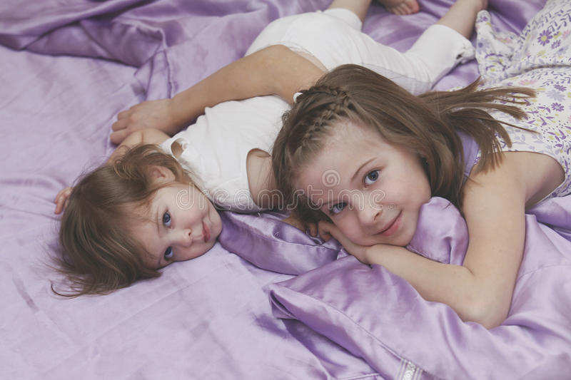 Children girls lying in bed. Children girls sisters lying in bed royalty free stock images