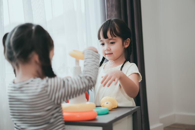 Children girls play a toy games in the room. Kids playing together with circular loop tower preschool and kindergarten education at home royalty free stock photo