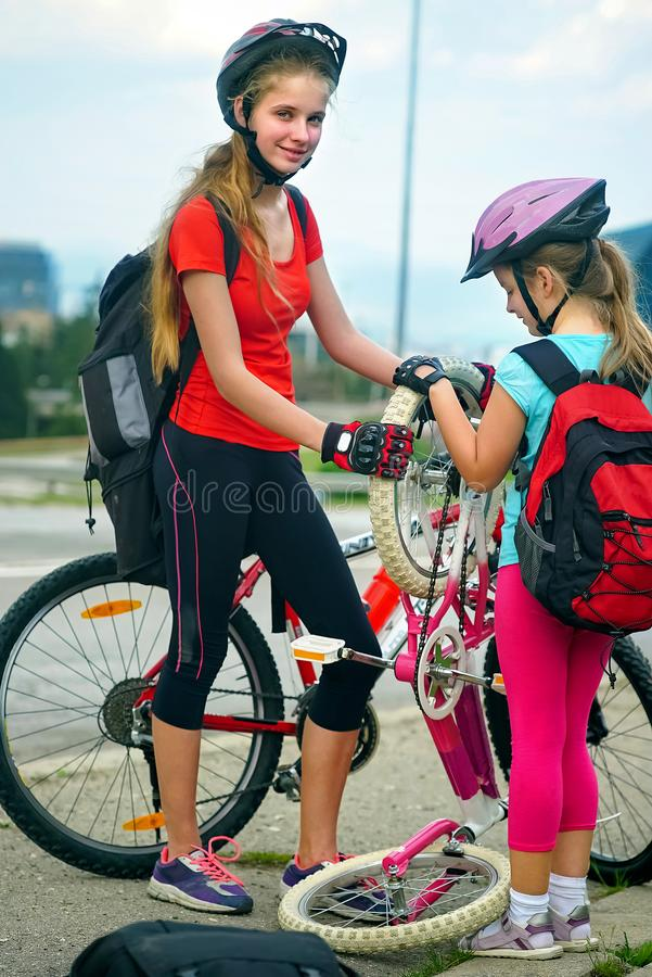 Children girls wearing helmet children repair bicycle. stock images