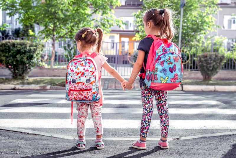 Children go to school, happy students with school backpacks and holding hands together. Cross the road, the concept of education with girls stock photography