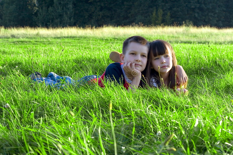 Children in grass stock images