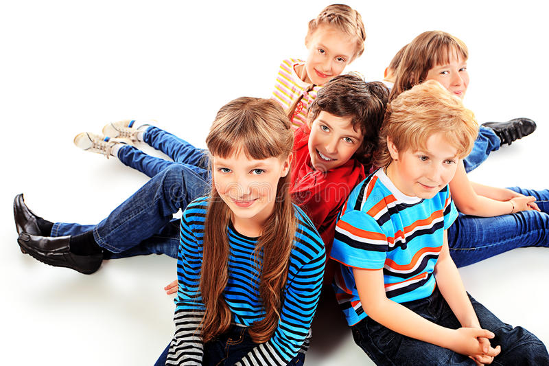 Children. Group of cheerful children sitting on a floor together. Isolated over white royalty free stock images