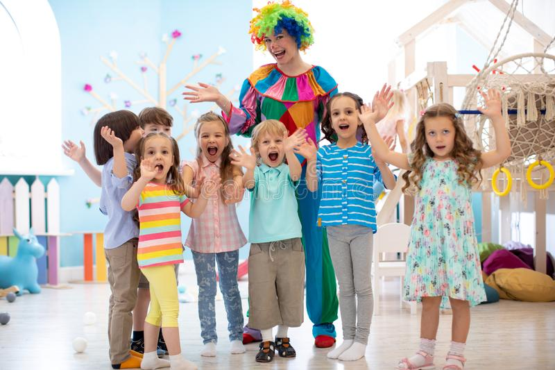 Children group with clown celebrating birthday party stock photo