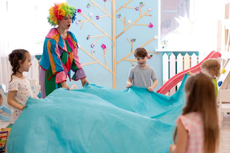 Children group have fun with clown on birthday party. Preschool children group have fun with clown on birthday party stock images